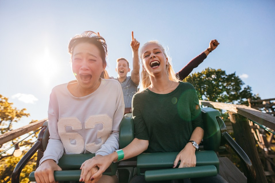 Enthusiastic young friends riding roller coaster ride