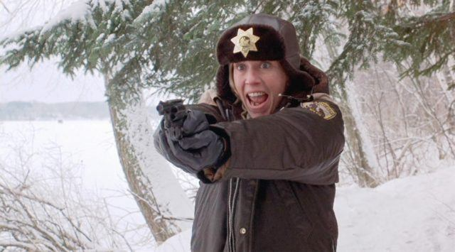 A police-woman yells, while holding her gun out in front of her in both hands