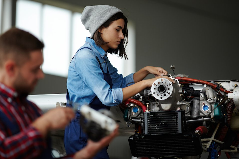 Side view portrait of modern woman repairing engine parts in workshop with man beside