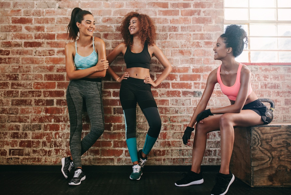 Happy young women talking in gym.