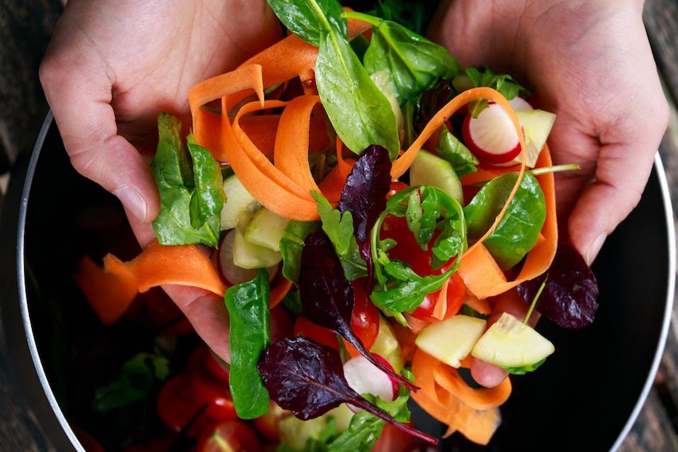 hands tossing a salad