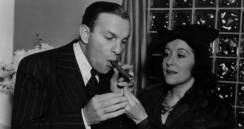 Gracie Allen is lighting a cigar for George Burns.