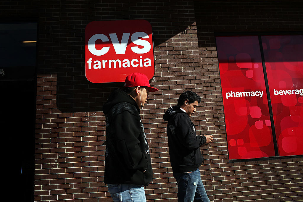 Two men walk by a bilingual sign for a CVS pharmacy in New Jersey