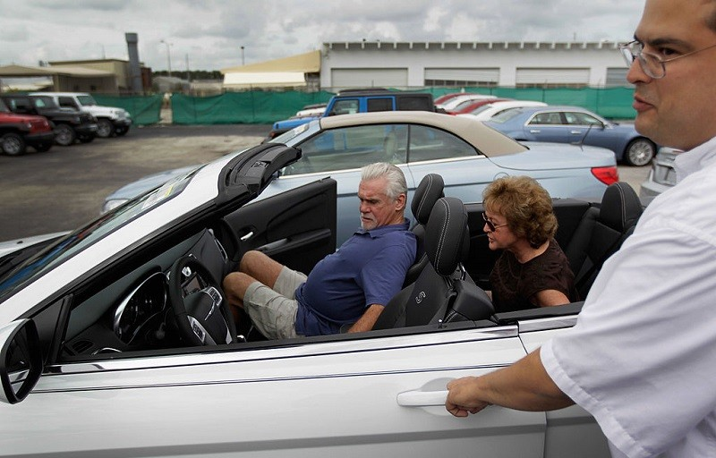 HOLLYWOOD, FL - OCTOBER 27: Salesman, JC Soto, (R) prepares to give Paul Mulcahy and Sarah Even a test drive in a new Chrysler car as they shop for a car on the sales lot of the Hollywood Chrysler Jeep dealership on October 27, 2011 in Hollywood, Florida. The sale of vehicles helped boost third quarter Gross domestic product (GDP), which grew at an inflation-adjusted annual rate of 2.5% from July through September, the strongest performance in a year.