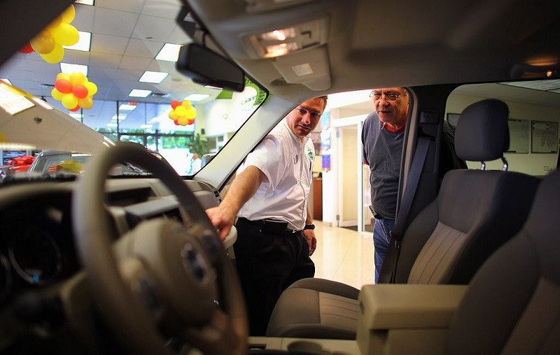 HOLLYWOOD, FL - OCTOBER 02: Chrysler sales consultant Doug Desloover (L) shows a Jeep Liberty to Lewis Colon at the Hollywood Chrysler Jeep car dealership on October 2, 2012 in Hollywood, Florida. Chrysler Group LLC reported that its sales last month rose 12% from a year ago for its best September since pre-recession 2007.