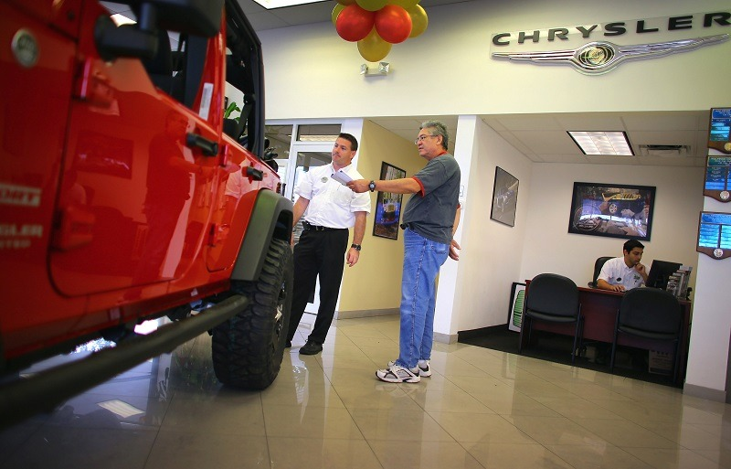HOLLYWOOD, FL - OCTOBER 02: Chrysler sales consultant Doug Desloover (L) shows a Jeep Wrangler to Lewis Colon at the Hollywood Chrysler Jeep car dealership on October 2, 2012 in Hollywood, Florida. Chrysler Group LLC reported that its sales last month rose 12% from a year ago for its best September since pre-recession 2007.