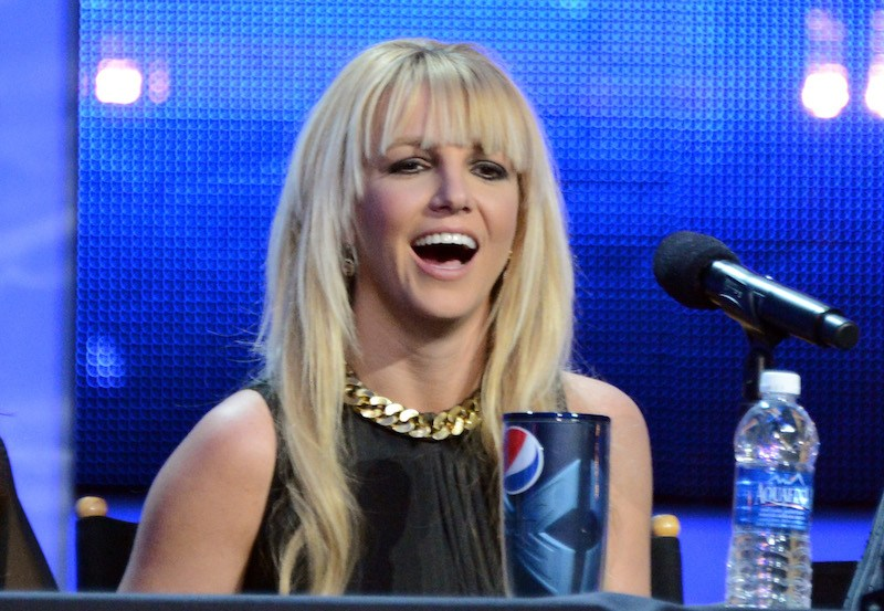 "Britney Spears sits behind a microphone at Fox's ""The X Factor"" season finale n"
