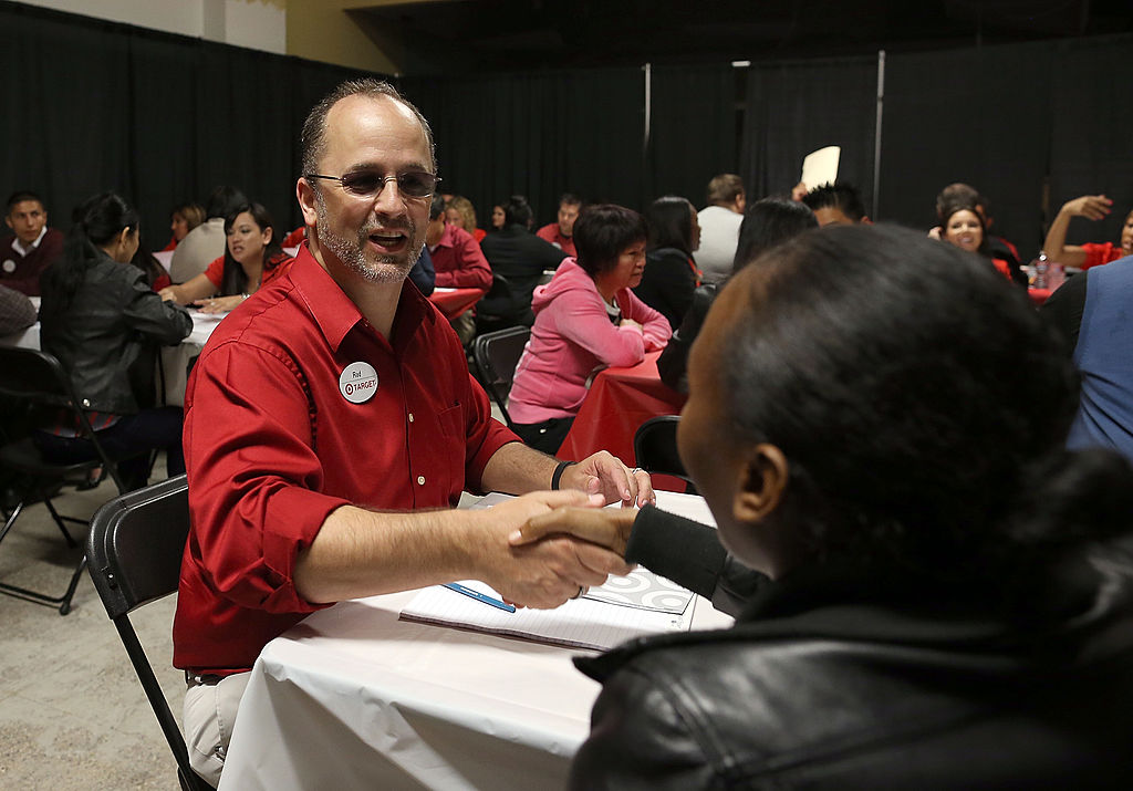 A Target employee greets a job seeker at the start of an interview during a job fair