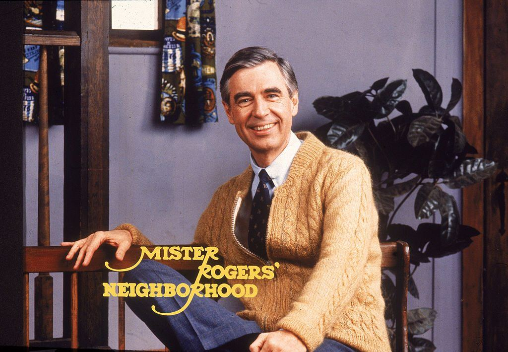 Fred Rogers sitting and posing with the words 'Mister Rogers' Neighborhood' across the image