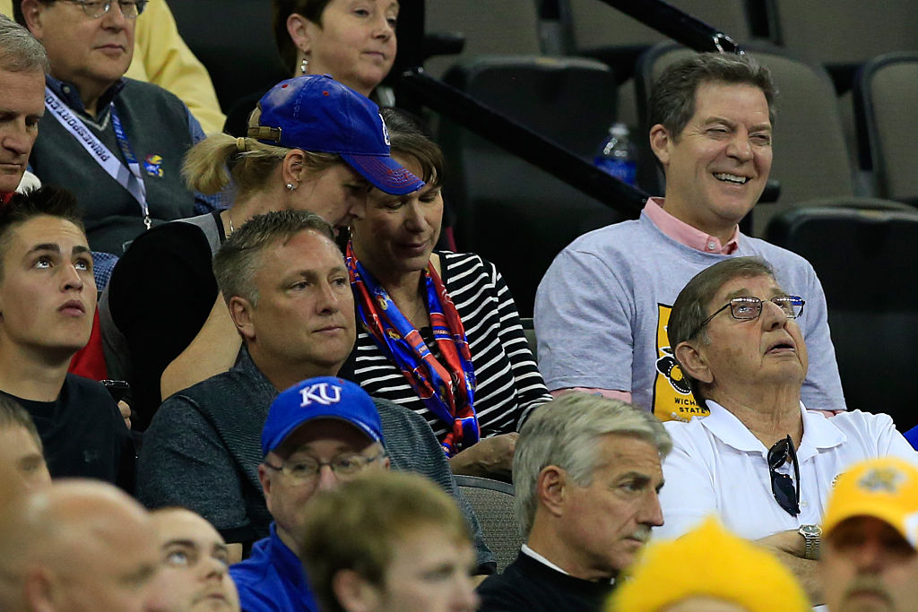Sam Brownback enjoys a college basketball game while his constituents stick through it