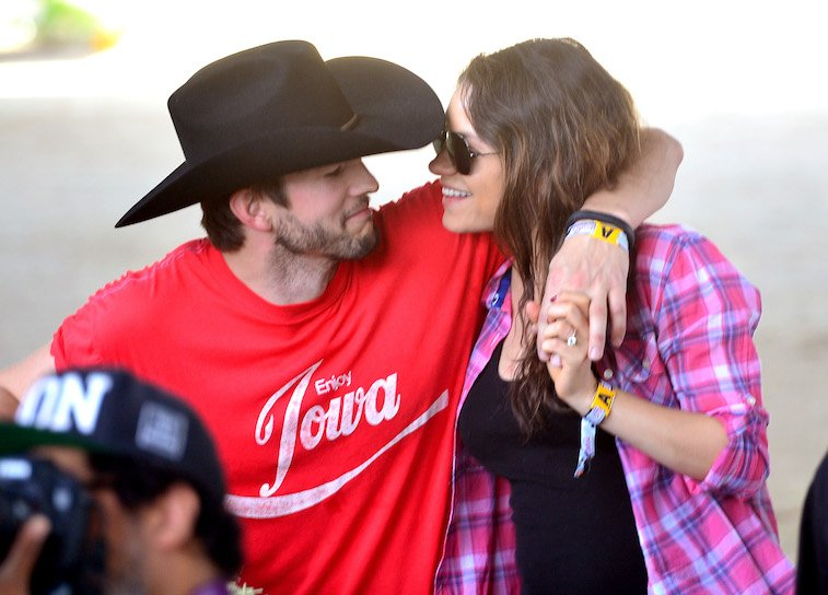 Actors Ashton Kutcher in a cowboy hat and Mila Kunis attend day 1 of 2014 Stagecoach