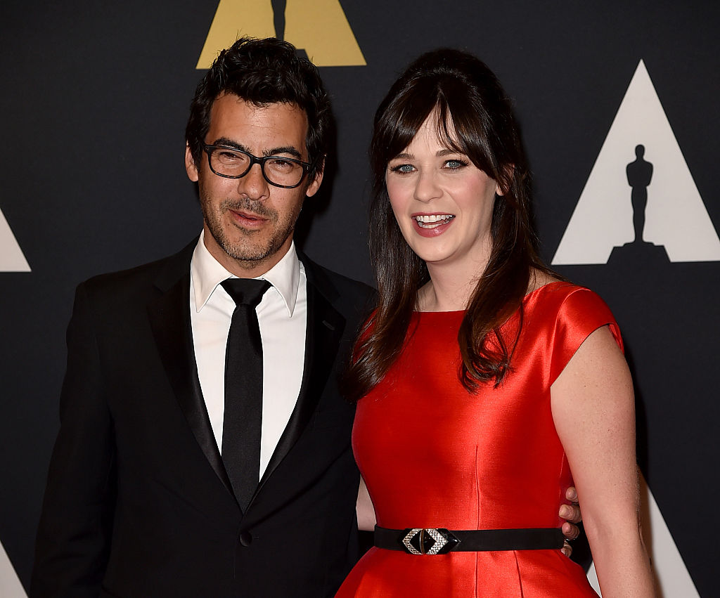 Zooey Deschanel in a red dress, smiling for the camera with her husband Jacob Pechenik on the red carpet