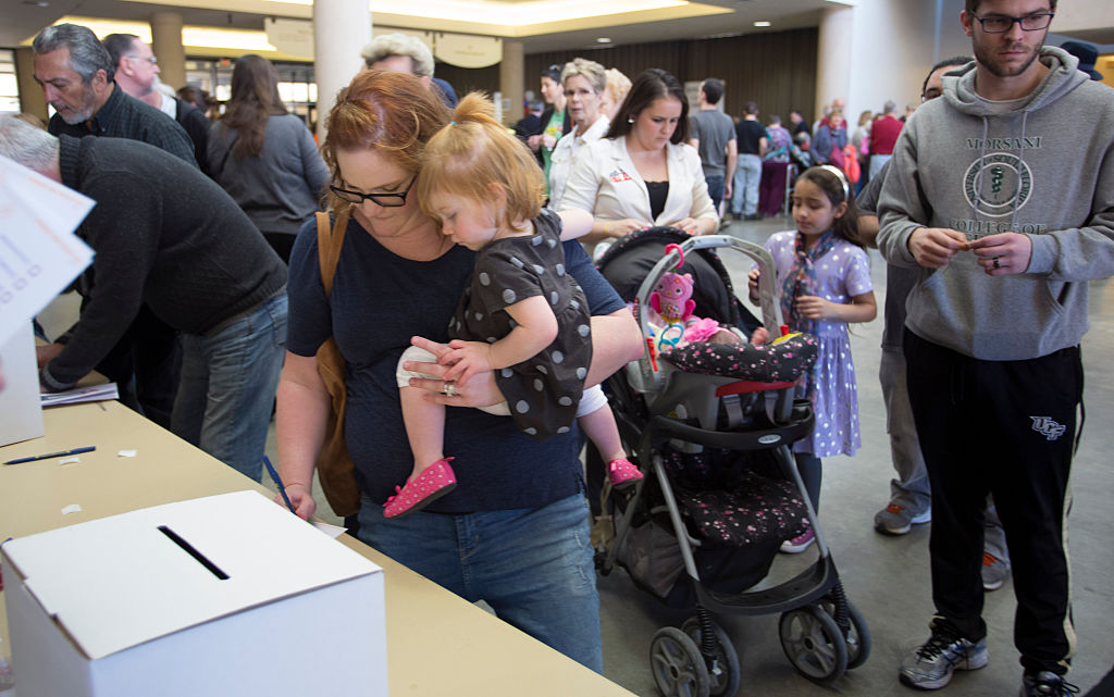 A woman holds her baby as she votes during the state's Republican caucus in Wichita, Kansas