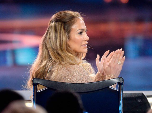 Jennifer Lopez claps her hands while sitting in a black chair.
