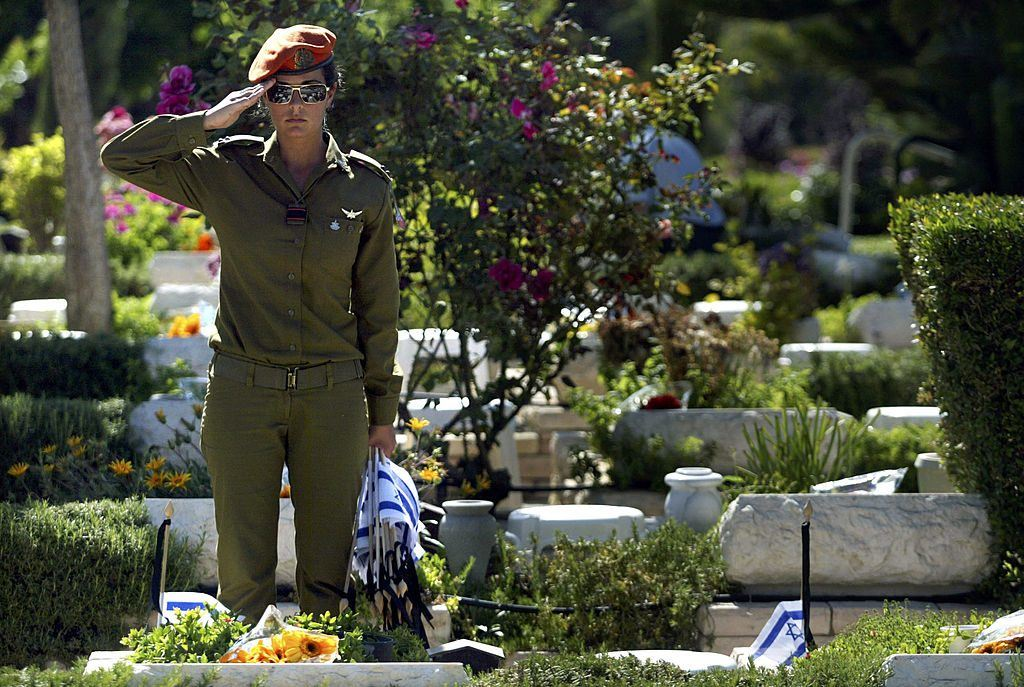 An Israeli soldier saluting in a cemetery surrounded by flowers and graves