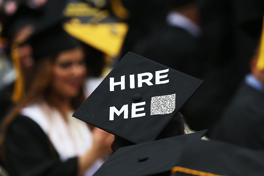 "A graduating student's cap says ""hire me,"" expressing concerns about paying off college tuition in coming years"