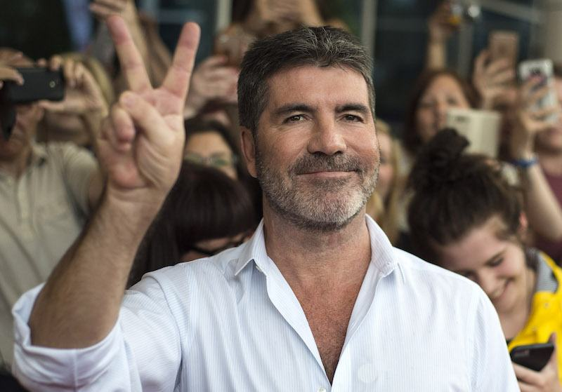 Simon Cowell flashes the peace sign for cameras