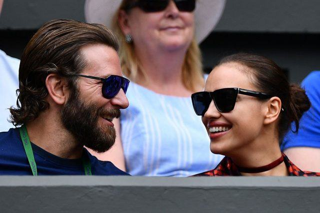 Bradley Cooper and Irina Shayk smiling at each other wearing sunglasses, sitting in the crowd at Wimbledon together.