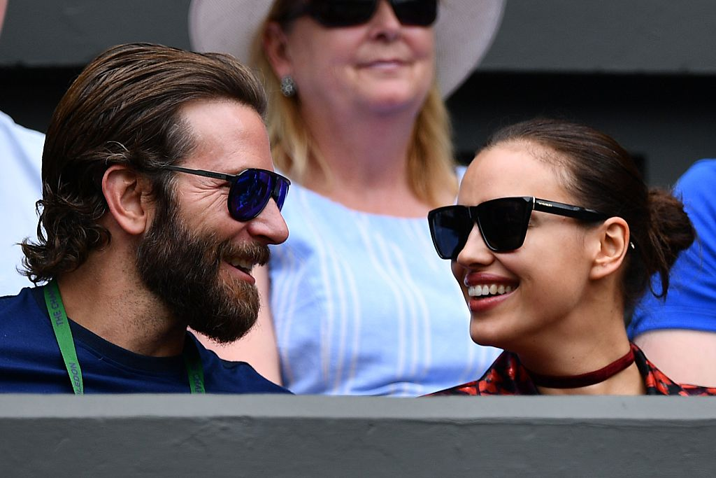 Bradley Cooper and Irina Shayk smiling at each other wearing sunglasses, sitting in the crowd at Wimbledon together