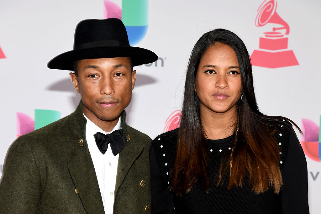 Pharrell wearing a tuxedo and wide-brim had, with his wife Helen on the red carpet