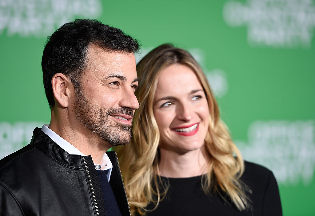 Jimmy Kimmel and Molly McNearney smiling on the red carpet together, looking off to the right of the frame