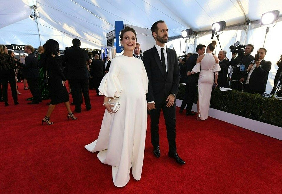 Natalie Portman and Benjamin Millepied on the red carpet, posing for photos in a white dress and tuxedo respectively