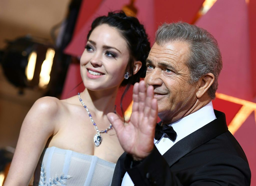 Rosalind Ross and Mel Gibson waving to the camera and smiling on the red carpet