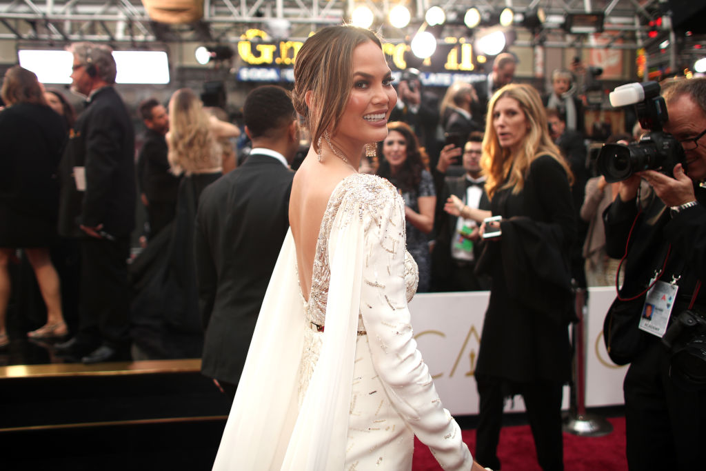 Chrissy Teigen in a white gown looks over her shoulder posing for cameras on the red carpet.