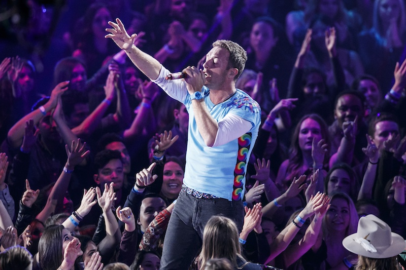 Singer-songwriter Chris Martin of Coldplay performs while fans reach up toward him