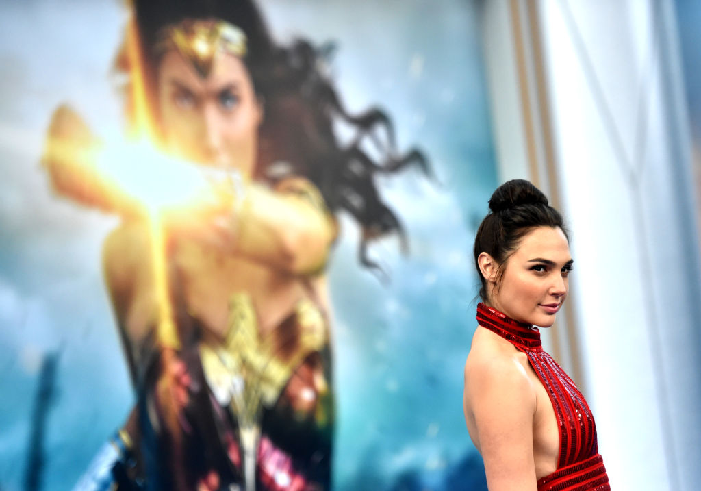 Gal Gadot poses in front of a poster for 'Wonder Woman'