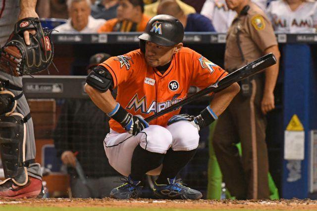 The baseball player kneels down while holding his baseball bat.