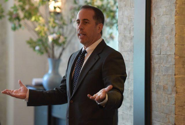 Jerry Seinfeld speaking with his hands raised up.