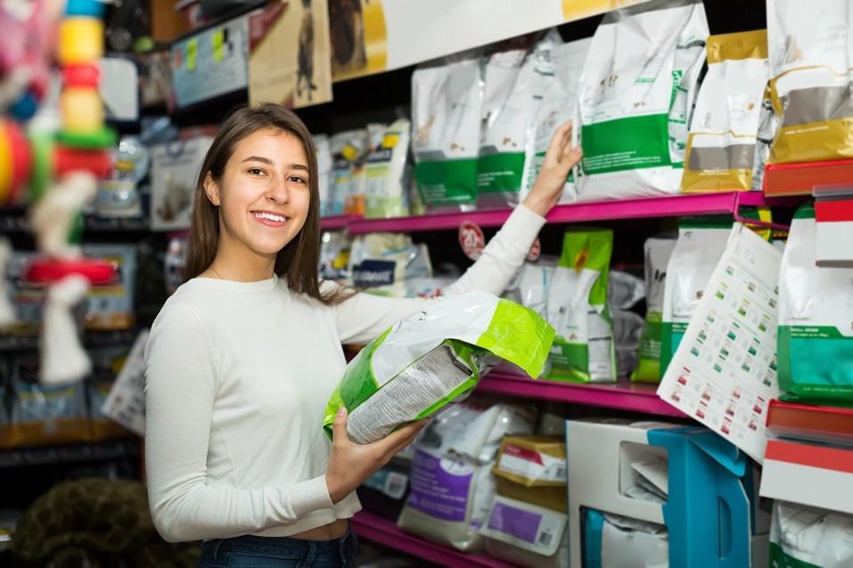 Girl choosing dry food in pet store