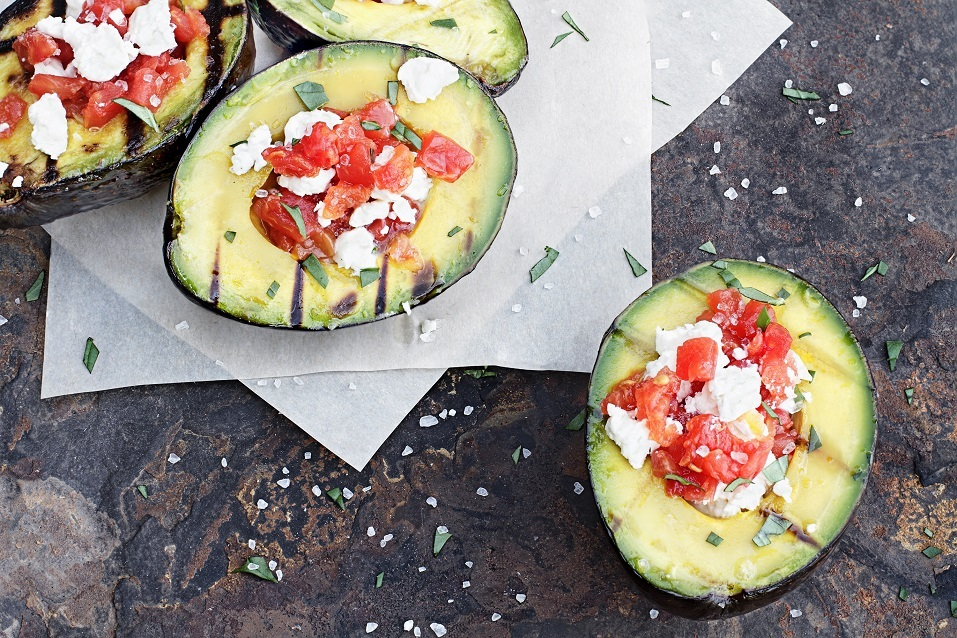 Grilled avocados filled with diced tomatoes