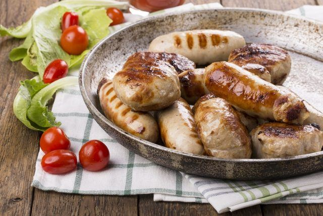 Grilled chicken sausages on a metal pan.