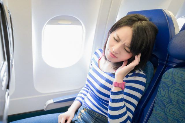 Happy young woman is sitting in the airplane, feel headache