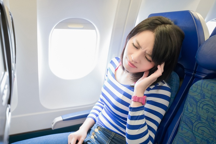 woman is sitting in the airplane with a headache