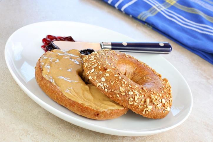 Healthy oat bran bagel spread with creamy peanut butter.