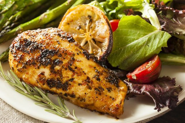 Lemon and Herb Chicken on a plate with salad and vegetables.