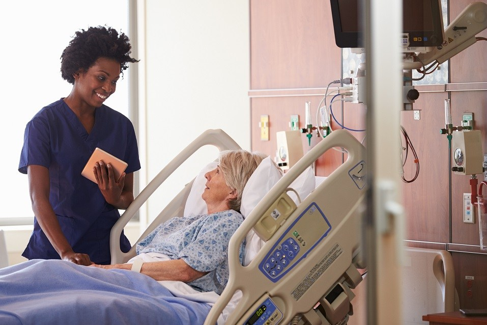 Nurse With Digital Tablet Talks To Senior Patient