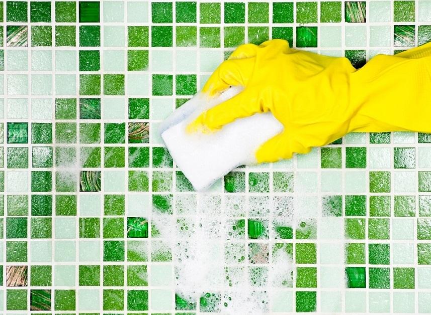 hand in yellow glove using sponge on tile