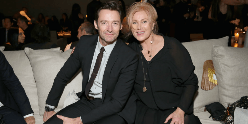 Hugh Jackman and Deborra-Lee Furness pose together sitting on a couch.