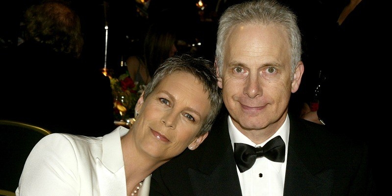 Jamie Lee-Curtis is resting her head on Christopher Guest's shoulder.