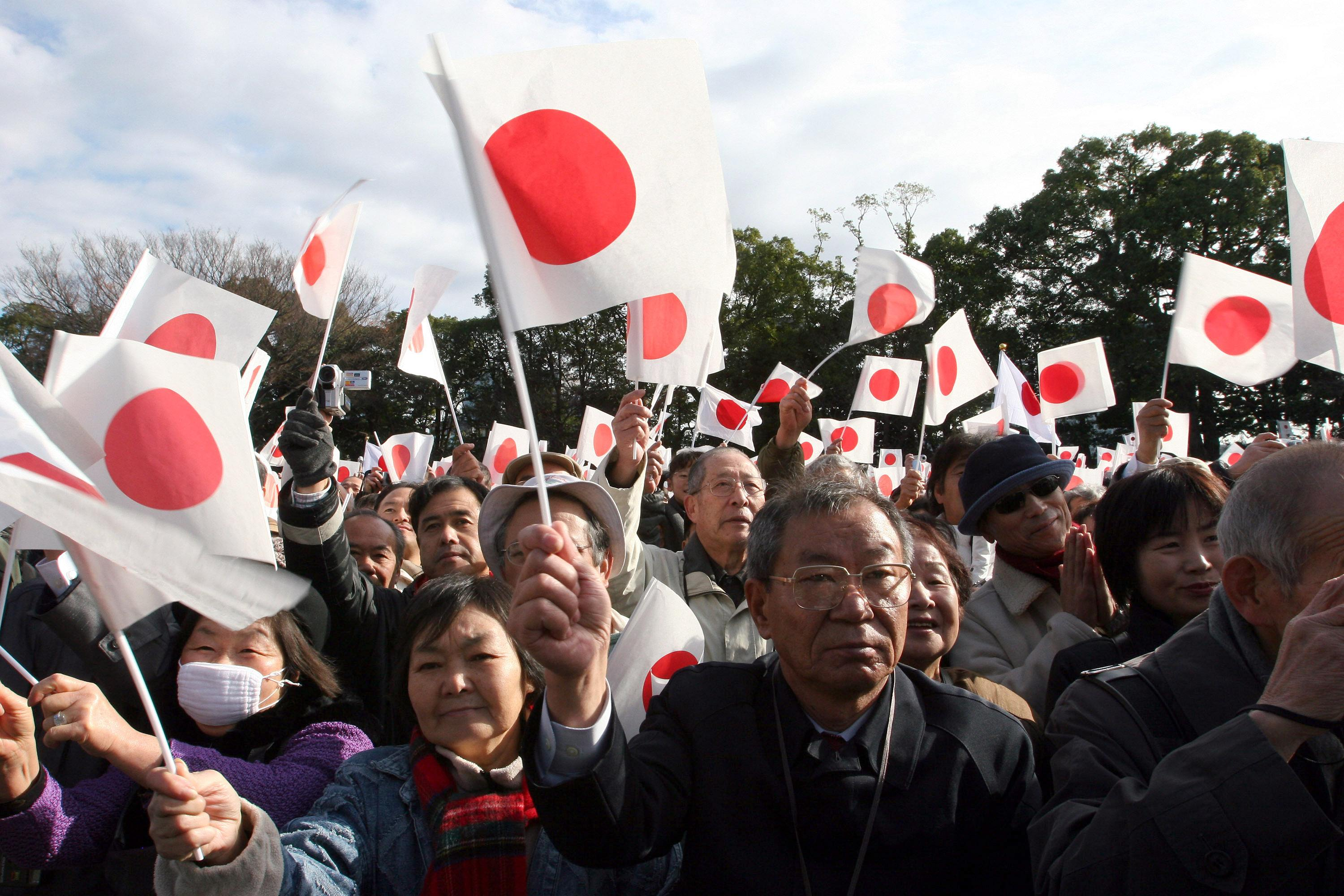 A crowd of people wave Japanese flags