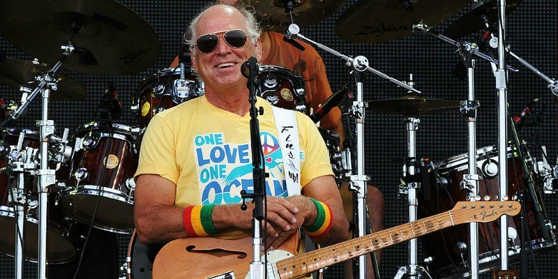 Jimmy Buffett is smiling and resting his hands on his guitar while on stage.