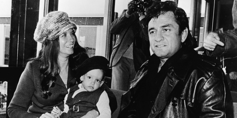 Johnny Cash and June Carter Cash are sitting next to each other. June is holding a baby.