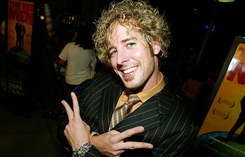 Jon Dalton is smiling and holding up two peace signs as he is wearing a striped suit.