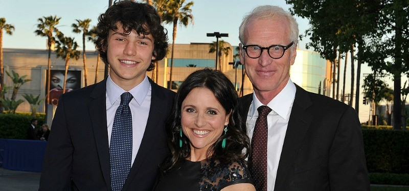 Julia Louis-Dreyfus (C) with son Charles Hall and husband Brad Hall pose together in black outfits.
