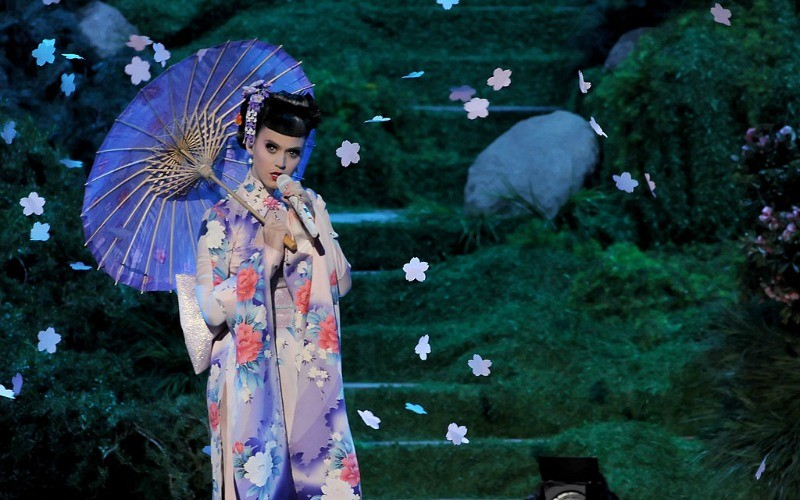 Katy Perry is dressed as a geisha and is holding an umbrella while singing on stage.