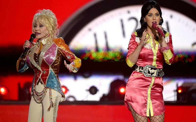 Katy Perry and Dolly Parton are singing on stage in colorful outfits.